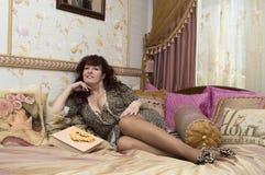 Die attraktive Frau wird auf einem Bett mit Fotoalben fotografiert. Lizenzfreies Stockfoto