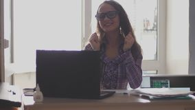 Die attraktive glückliche Geschäftsfrau, welche die Brillen arbeiten mit Computer im Büro trägt, genießt erfolgreiche Arbeit Daum stock video