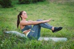 Die attraktive junge Frau der Eignung, die auf dem Gras in einem Park tun sitzt Stockbild