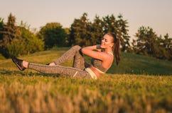 Die attraktive junge Frau der Eignung, die auf dem Gras in einem Park tun sitzt Stockfotos
