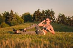 Die attraktive junge Frau der Eignung, die auf dem Gras in einem Park tun sitzt Stockfotografie