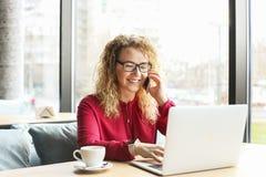 Die attraktive junge Frau, die an der Kaffeestube mit ihrem modernen Laptop, trinkender Cappuccino, sprechend am Telefon sitzt, e Stockfoto