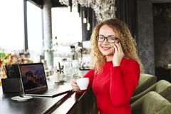 Die attraktive junge Frau, die an der Kaffeestube mit ihrem modernen Laptop, trinkender Cappuccino, sprechend am Telefon sitzt, e Stockfotos