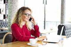 Die attraktive junge Frau, die an der Kaffeestube mit ihrem modernen Laptop, trinkender Cappuccino, sprechend am Telefon sitzt, e Lizenzfreie Stockfotografie