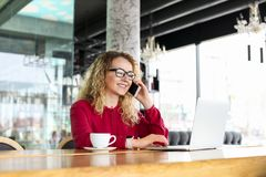 Die attraktive junge Frau, die an der Kaffeestube mit ihrem modernen Laptop, trinkender Cappuccino, sprechend am Telefon sitzt, e Lizenzfreie Stockbilder