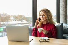 Die attraktive junge Frau, die an der Kaffeestube mit ihrem modernen Laptop, trinkender Cappuccino, sprechend am Telefon sitzt, e Lizenzfreie Stockfotos