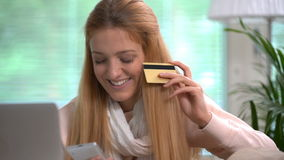 Die attraktive junge Frau, die on-line-Käufe tut, benutzt Goldkreditkarte Langsame Bewegung stock video footage