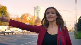 Die attraktive junge Frau, die nach einem Aufzug, stehend auf dem Bürgersteig in der Stadt sucht, kann einen Aufzug erhalten nich stock video footage