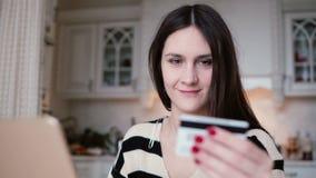 Die attraktive junge lächelnde Frau benutzt Plastikkreditkarte online kaufend mit Laptop Lizenzfreie Stockbilder