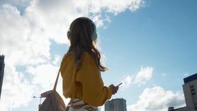 Die attraktive lächelnde junge Frau trägt Kopfhörer hörend Musik auf dem Musikspieler an unscharfem Stadthintergrund stock footage
