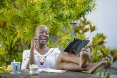 Die attraktive schwarze afroe-amerikanisch Frau, die mit digitaler Tablette draußen am Café arbeitet, entspannte sich und nett im Stockfoto