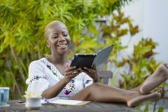 Die attraktive schwarze afroe-amerikanisch Frau, die mit digitaler Tablette draußen am Café arbeitet, entspannte sich und nett im Stockbild