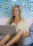 Die attraktive und elegante blonde Frau, die online arbeitet, entspannte sich mit Laptop-Computer als digitaler Nomade und Social Lizenzfreies Stockfoto