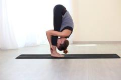 Die attraktiven Frauen, die Yoga tun, trainiert zu Hause Stockfoto