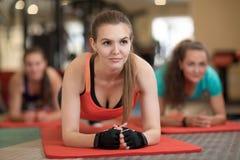 Die attraktiven jungen Frauen, die auf ihren Armen tun Übung für Hinterteile sich lehnen, mischt an der Turnhalle mit Lizenzfreie Stockfotos