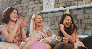 Die attraktiven multi ethnischen Damen, die eine Geburtstagsfeier zu Hause in einem modernen Schlafzimmer feiern, haben eine Pyja stock video footage