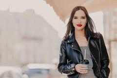 Die Außenaufnahme des attraktiven tausendjährigen weiblichen Modells mit Make-up, gekleidet in der stilvollen Lederjacke, trinkt  stockfotos