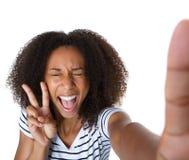 Die aufgeregte junge Frau, die Frieden zeigt, unterzeichnen herein selfie Lizenzfreies Stockfoto
