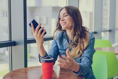 Die aufgeregte lächelnde glückliche Frau, die einen Rest in einem Café hat, betrachtet sie Schirm ihrer notific Smartphonetelefon lizenzfreie stockfotos