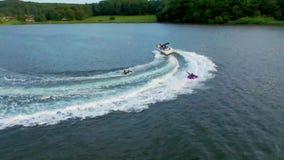 Die aufgeregten glücklichen Menschen, die aufblasbaren Wasserschlauch reiten, schieben Anziehungskraft mit Motorboot im wunderbar stock video footage