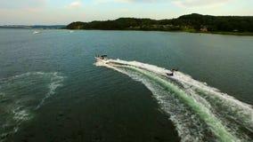 Die aufgeregten glücklichen Menschen, die aufblasbaren Wasserschlauch reiten, schieben Anziehungskraft mit Motorboot, wenn sie Lu stock video footage