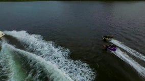 Die aufgeregten glücklichen Menschen, die aufblasbaren Wasserschlauch reiten, schieben Anziehungskraft mit Motorboot, wenn sie Lu stock footage