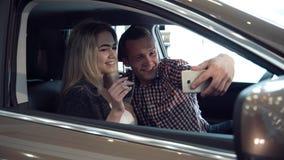 Die aufgeregten jungen Paare, die einen Neuwagen kaufen und machen selfie Lizenzfreie Stockbilder