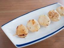 Die aufgespießten Japaner salzen reife Kamm-Muscheln Stockfotos