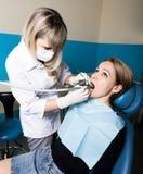 Die Aufnahme war am weiblichen Zahnarzt, den Doctor die Mundhöhle auf Zahnverfall überprüft Kariesschutz Doktor setzt sich stockbilder