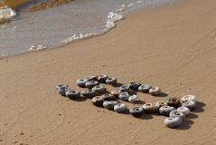 Die Aufschrift 'Meer 'wird durch kleines Meer-shellson das mit gelbem Sand geschrieben stockbild