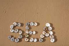 Die Aufschrift 'Meer 'wird durch kleines Meer-shellson das mit gelbem Sand geschrieben stockfoto