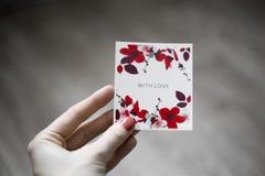 Die Aufschrift 'mit Liebe 'auf einem weißen Hintergrund mit Blumen, eine Hand mit dem unterzeichneten Papier Hölzerner Hintergrun stockbild