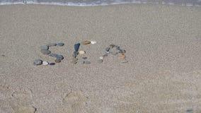 Die Aufschrift auf dem Sand des Meeres Stockbild