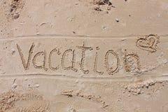 Die Aufschrift auf dem Strandsand - Ferien stockfotos