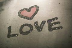 Die Aufschrift auf dem verschwitzten Glas - Liebe und rotes Herz Lizenzfreies Stockfoto
