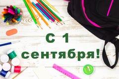 Die Aufschrift auf russisch ist am 1. September Schulbedarf auf einem weißen hölzernen Hintergrund mit einem leeren Raum für Aufs Stockfotografie