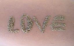 Die Aufschrift des Sandes fasst Liebe auf der Haut ab lizenzfreie stockbilder