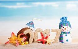 Die Aufschrift 2017 im Sand mit einem Weihnachtenschneemann, einem Koks und einem Starfish Stockfotografie