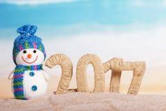 Die Aufschrift 2017 im Sand und im Schneemann auf dem Hintergrund des Meeres Stockfotos