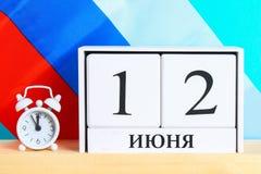 Die Aufschrift ist am 12. Juni, der Tag von Russland Hölzerner weißer Kalender auf dem Hintergrund der Flagge von Russland Lizenzfreies Stockbild