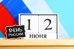 Die Aufschrift ist am 12. Juni, der Tag von Russland Hölzerner weißer Kalender auf dem Hintergrund der Flagge von Russland Lizenzfreies Stockfoto
