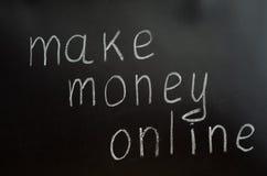 Die Aufschrift ist weiße Kreide auf einer Tafel: verdienen Sie Geld on-line Stockbilder