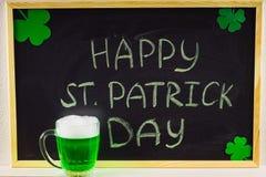 Die Aufschrift mit grüner Kreide auf einer Tafel: Glücklichen St Patrick Tag Weißer Klee-Blätter Ein Becher mit grünem Bier Stockbilder