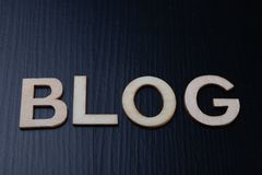 Die Aufschrift wird von den Buchstaben vereinbart, die auf dem Tisch vom Holz herausgeschnitten werden Das Wort - Blog stockbild