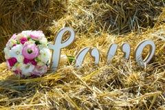 Die Aufschriftliebe mit einem Brautblumenstrauß Lizenzfreies Stockfoto