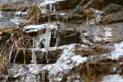 Die Auftaueneiszapfen mit fallenden Wasser fallen in die Berge Lizenzfreies Stockbild
