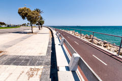 Die Aussicht des Meeres und der Promenade mit Palmen Stockbild