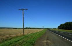 Die Automobilseite der gepflasterten Straße Telegrafische hölzerne Pfosten und ein schräges Feld entlang der Straße Stockbilder