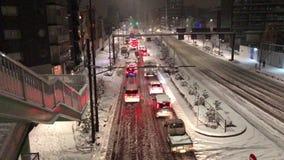 Die Autos, die in Tokyo als Fußgänger fest sind und der Verkehr kämpft während eines seltenen Schneesturms stock footage