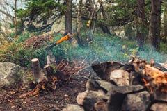 Die Axt fest im Klotz nahe dem Feuer stockfotos